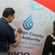 "Attendees sign the ""Brought To You By Water"" symbolic beach ball, naming summer activities that rely on a safe and reliable water supply. Photo: Water Authority. Brought To You"