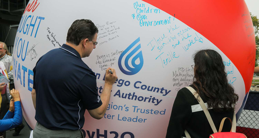 """Attendees sign the """"Brought To You By Water"""" symbolic beach ball, naming summer activities that rely on a safe and reliable water supply. Photo: Water Authority. Brought To You"""