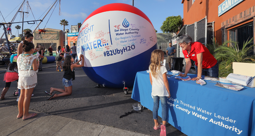 "Sunset Market in Oceanside welcomed the ""Brought To You By Water"" giant beach ball ambassador, accompanied by Water Authority community outreach staff who provided information and answered questions about the region's water supply. Photo: Authority"