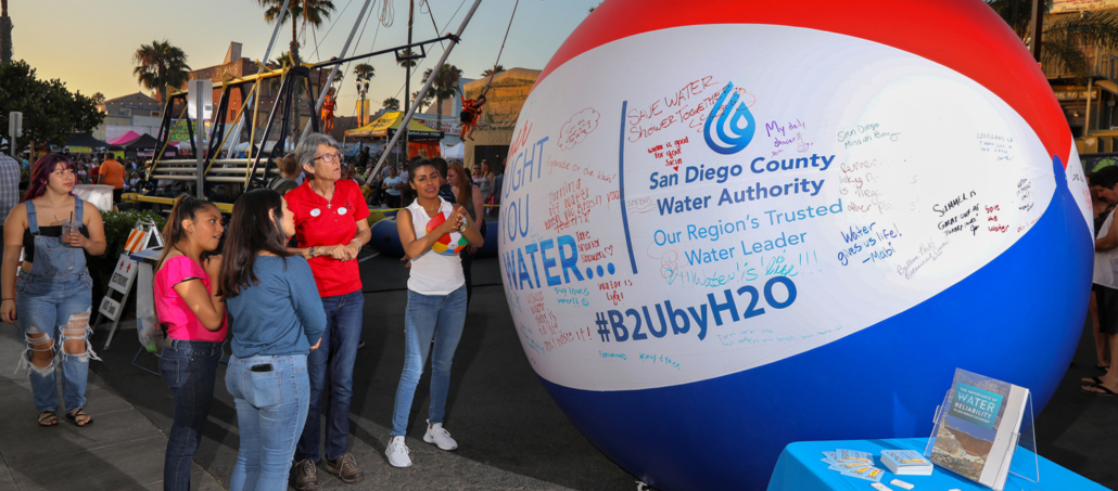 Visitors to the Oceanside Sunset Market get a close look at the topics written on the 'Brought To You By Water' beach ball. Photo: Charlie Neuman, Water Authority