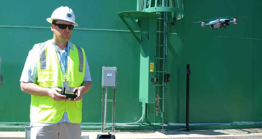 Alexander Schultz, Otay Water District geographic information systems technician, operates a drone in front of a district water storage tank. Photo: Otay Water District