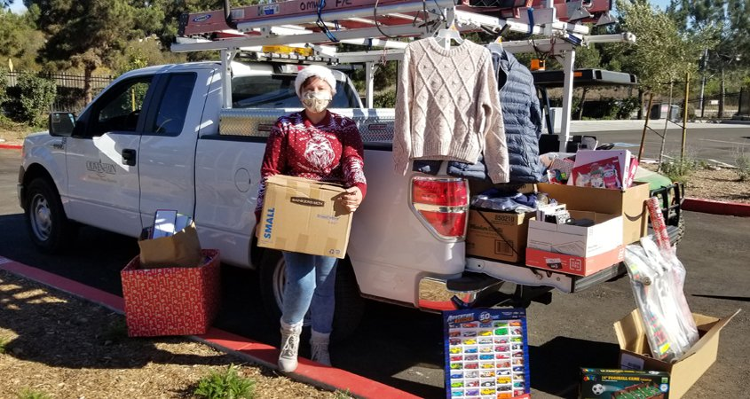 Teresa Chase helps load up donations from Olivenhain Municipal Water District employees. They are playing Santa Claus to a family of seven, a local senior, and a veteran in its annual adopt-a-family effort, and filled a truck bed with donations for the San Diego Humane Society. Photo: Olivenhain Municipal Water District