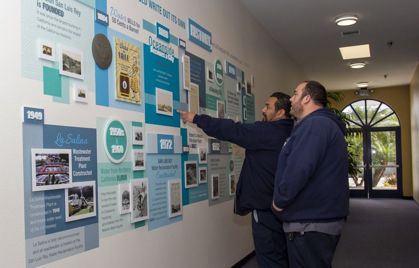 City of Oceanside employees Carlos Raymundo (closest) and Shawn Alonzo view the award-winning Pure Water Oceanside wall art project. Photo: City of Oceanside