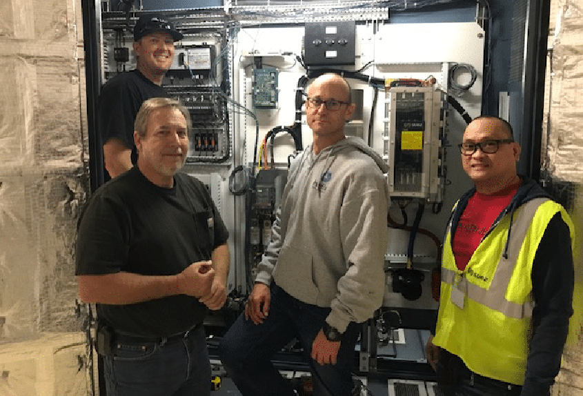 Helix's ozone project team (pre-pandemic) in front of the rebuilt power supply unit.
